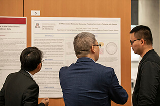 Symposium Attendees Discussing One of the Research Posters