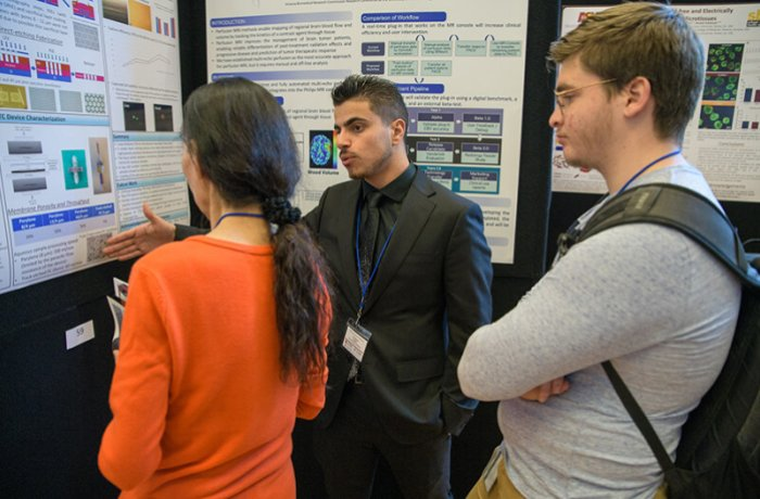 A Researcher Discusses His Findings with Attendees of the Conference