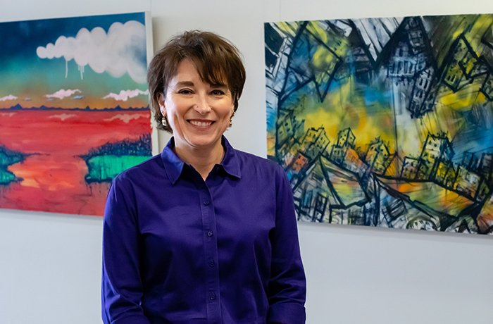 Cindi Standley, PhD, Stands in Front of Two Paintings in the HSEB