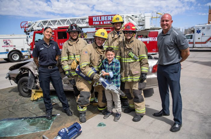 Simulated crash training crews with Glendale Fire paramedic Alex Matthews (left), her son, Jamison (holding jaws-of-life device), and Mesa and Gilbert Fire crews. Alex and Jamison were in a motor vehicle accident in December 2012, where Alex used the EPIC-TBI prehospital care guidelines to help save the life of her son.