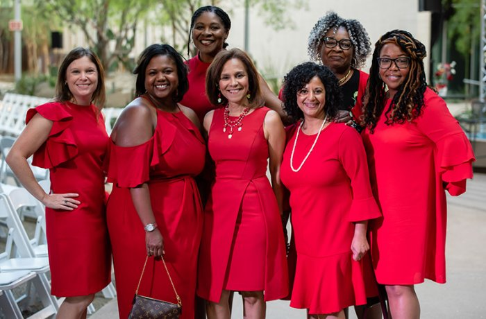A Group of Women, Adorned in Red, Pose at the Red Dress Event