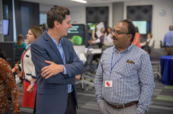 Tim Marlowe, PhD, Talks with an Attendee at the Research Office Open House