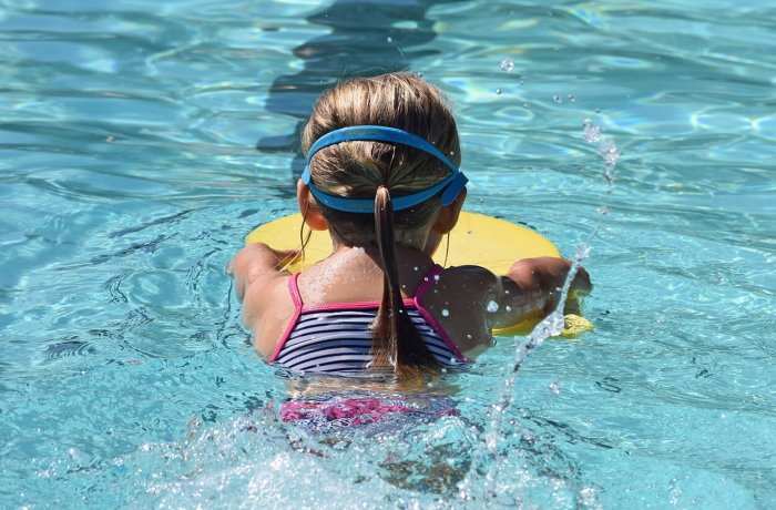 A Child Swims in a Swimming Pool