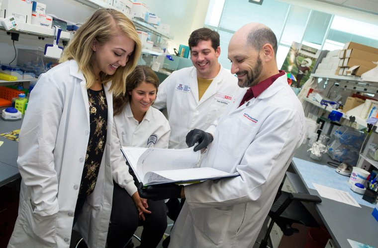 Katherine Giordano (Far Left) in the Lab with Dr. Jonathan Lifshitz (Far Right) and Others